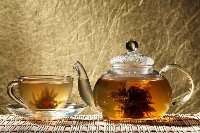 Xícara de chá ao lado de bule de vidro
