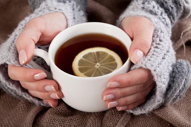 Imagem de mãos femininas com agasalho segurando xícara de chá