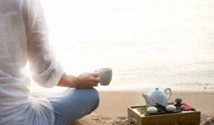 Woman meditating and drinking tea on beach