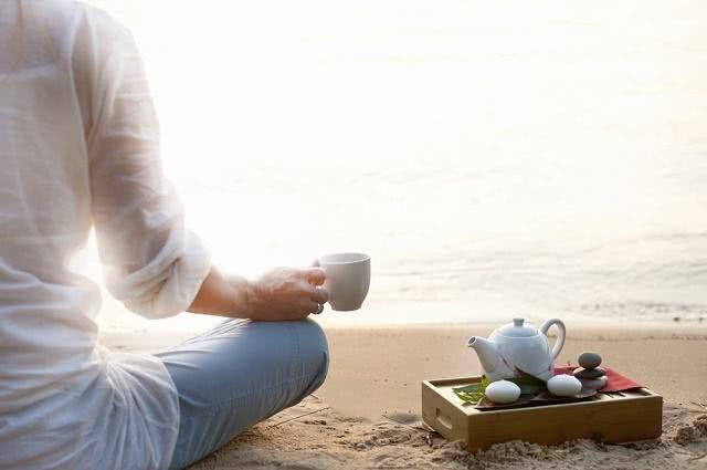 Imagem de mulher segurando xícara de chá e meditando em praia