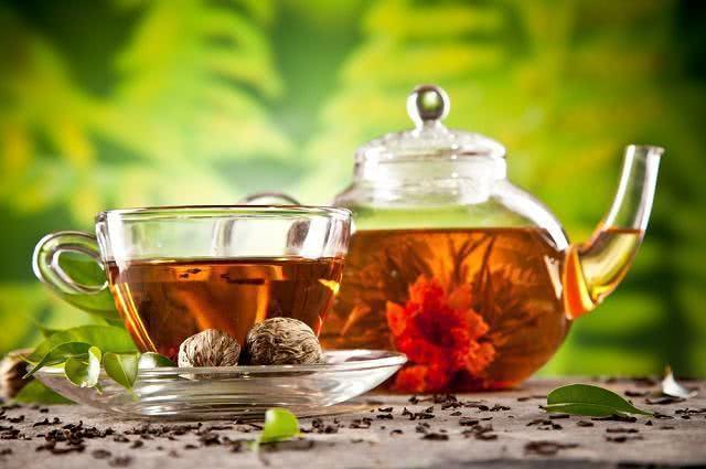 Imagem de bule de vidro com chá de florescência