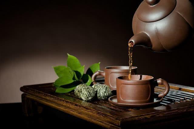 Imagem de bule e xícaras de barro com chá