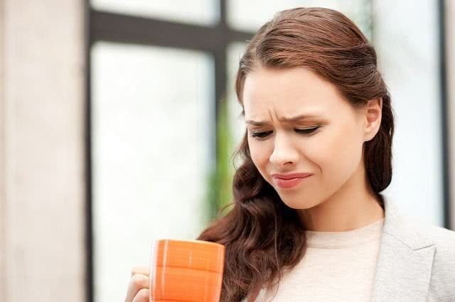 Imagem de mulher com semblante negativo olhado para caneca