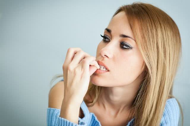 Imagem de mulher nervosa mordendo as unhas