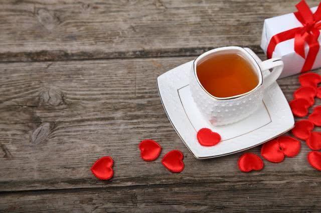 Imagem de xícara de chá e corações vermelhos decorativos